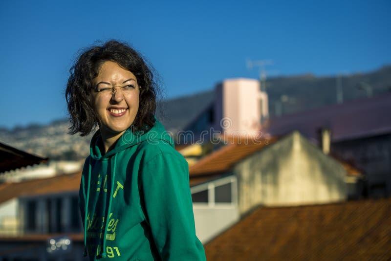年轻白种人女孩画象坐在丰沙尔市的屋顶的上大阳台 免版税库存照片