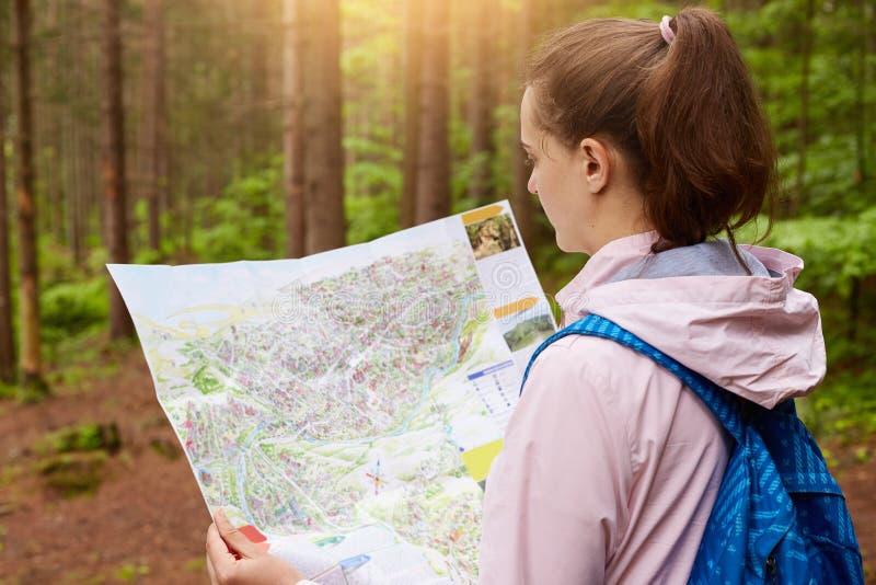 年轻白种人女性与蓝色背包和地图外形在木头,看地图的徒步旅行者和设法发现方式,有 免版税图库摄影