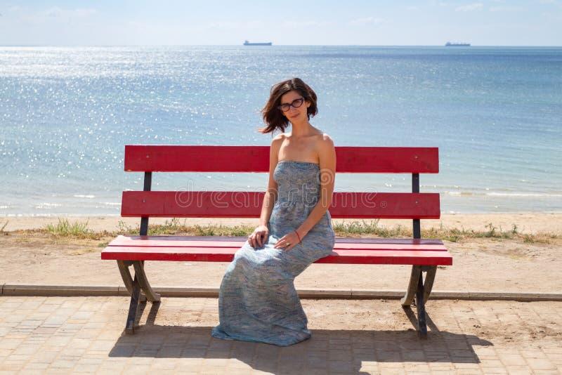 年轻白种人女性模型坐一条红色长凳 在背景海滩和海 免版税图库摄影