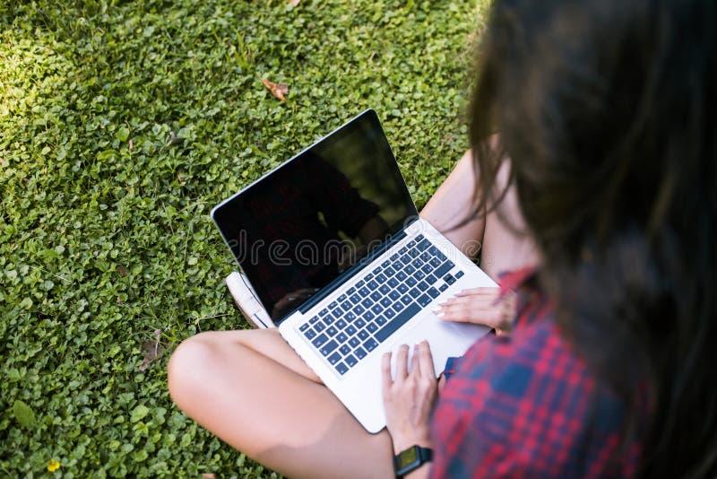 年轻白种人妇女佩带的格子衬衫播种的顶端后方的看法,坐在膝上型计算机个人计算机前面的草,运转在她 库存图片