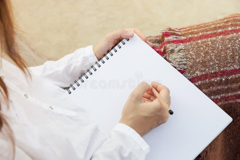年轻白种人妇女在公园坐长凳拿着在写生簿的铅笔图 方格的棕色红色灰色格子花呢披肩 艺术速写 库存图片