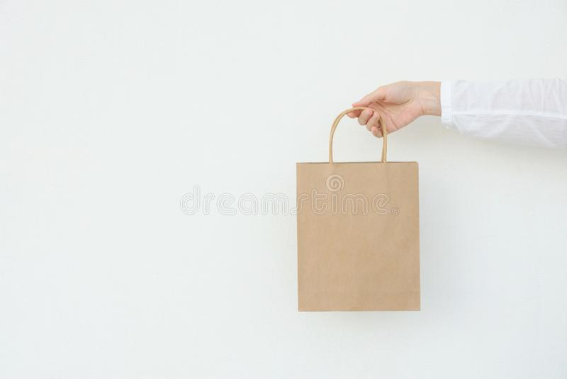年轻白种人妇女在手中举行棕色工艺纸袋的空的空白嘲笑在白色墙壁背景 圣诞节新年 免版税库存照片