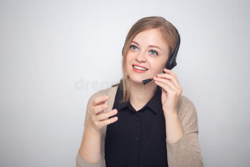 年轻白种人妇女在耳机电话在电话中心谈话 免版税图库摄影