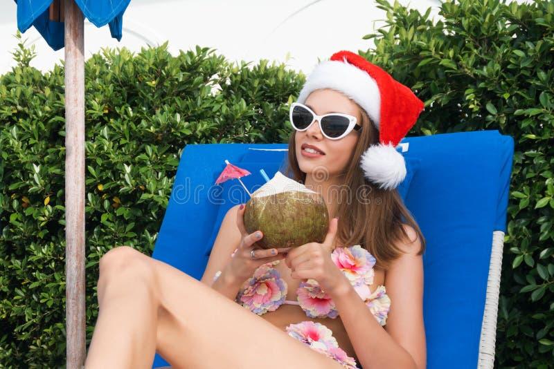 年轻白种人妇女在Sunbed的圣诞老人帽子饮用的椰子 免版税库存图片