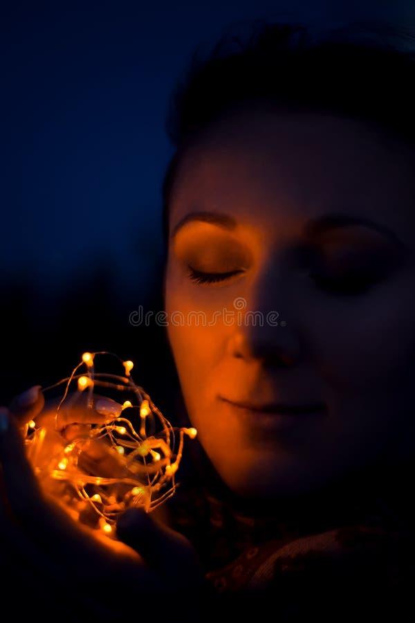 年轻白种人妇女外面在晚上在她的手上的拿着圣诞灯有她的眼睛的闭合和微笑的认为 免版税库存照片
