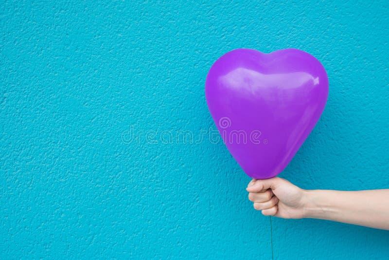 年轻白种人妇女女孩拿着在绿松石被绘的墙壁背景的手中紫色心形的气球 爱慈善 免版税库存照片