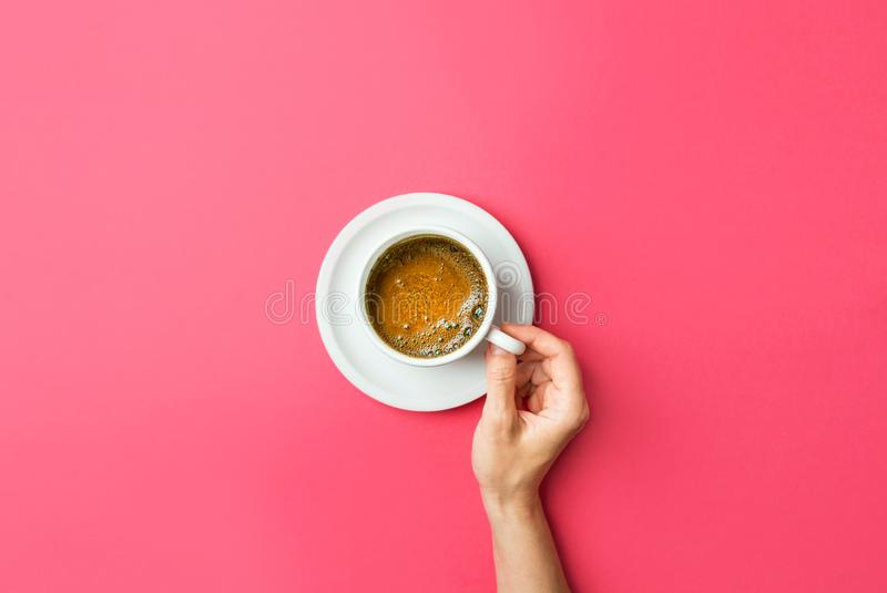 年轻白种人妇女手拿着白色杯子用与泡沫似的crema的新近地煮的咖啡在梯度紫红色的桃红色的茶碟 库存图片