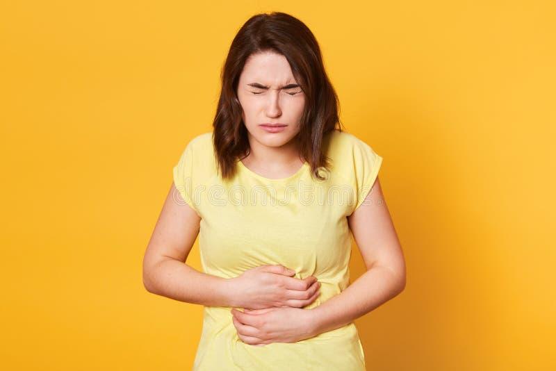 年轻白种人妇女接近的画象有可怕的stomachache的在黄色背景,吃东西到期了,有醉, 库存图片