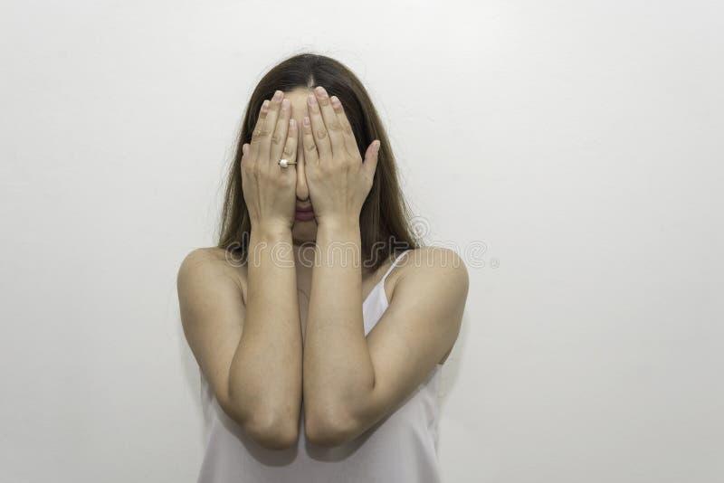 年轻白种人妇女掩藏她的与她的棕榈的眼睛 免版税库存图片