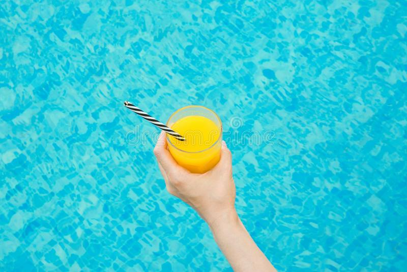年轻白种人妇女由游泳池拿着杯与镶边秸杆的新近地被按的热带水果橙汁 免版税库存图片