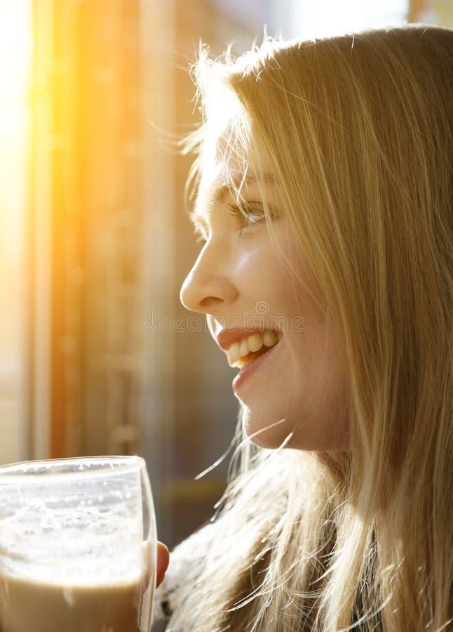 年轻白种人妇女藏品杯子和饮用的拿铁在咖啡馆 都市舒适咖啡馆的女性 从户外的旁边射击 免版税库存图片