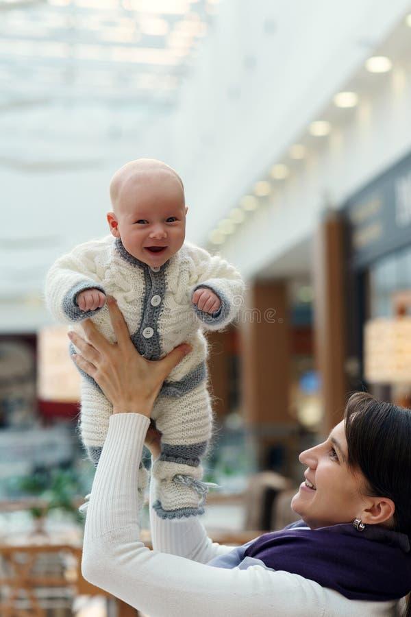 年轻白种人妈妈使用与她逗人喜爱的快活的男婴,投掷他并且在公共场所再捉住 图库摄影