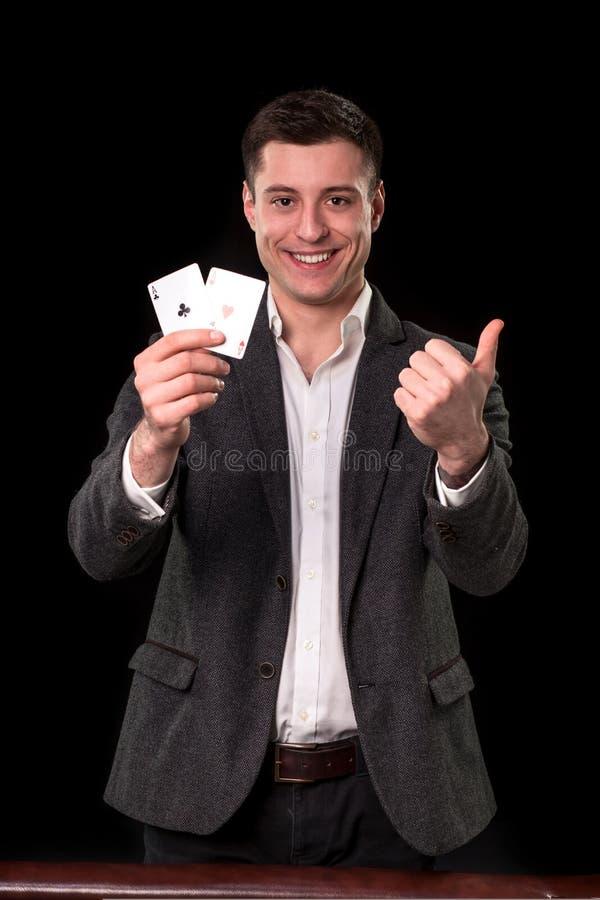 年轻白种人拿着两一点和显示赞许与微笑的人佩带的衣服在他的手上手势在黑色 库存图片