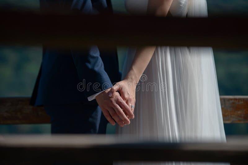 年轻白种人播种的,无固定职业的摄影师式,私有握手的射击新娘和新郎 免版税库存图片