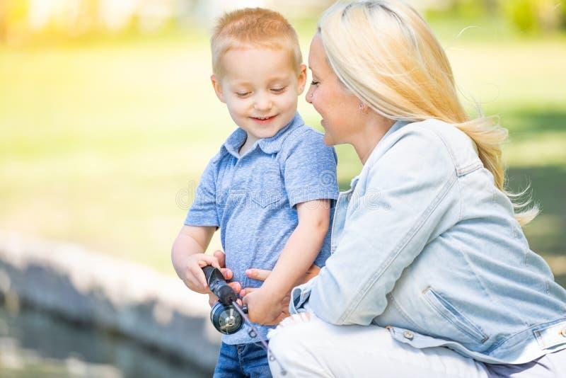 年轻白种人母亲和儿子有乐趣渔在湖 免版税库存图片