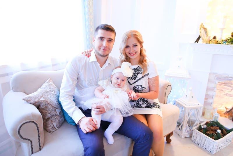 年轻白种人父母与女儿坐近沙发装饰了壁炉 免版税库存图片