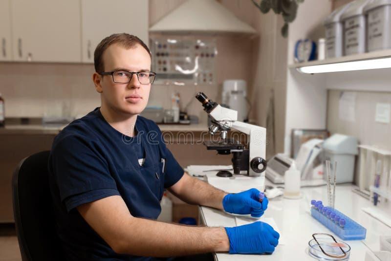 年轻白种人男性科学家、医护人员、技术或者大学生工作画象在现代生物实验室 免版税图库摄影