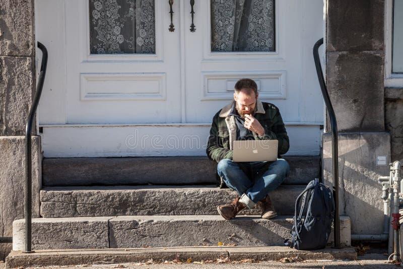 年轻白种人男性,数字游牧人,坐和使用他的膝上型计算机,苹果计算机Macbook,得到wifi互联网连接在老蒙特利尔 库存照片