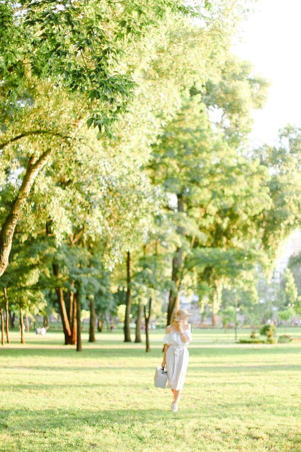 年轻白种人走在有袋子的公园的妇女佩带的帽子在好日子 免版税库存照片