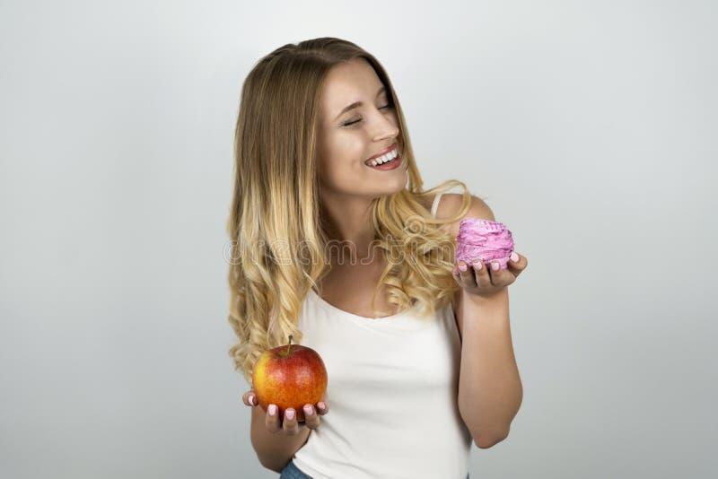 年轻白肤金发的可爱的妇女在一只手和桃红色鲜美杯形蛋糕上的拿着水多的红色苹果在其他手被隔绝的白色 免版税库存图片
