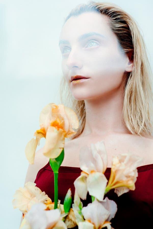 年轻白肤金发的可爱的妇女的画象有时尚外籍人金子的做站起来与虹膜花 免版税库存图片