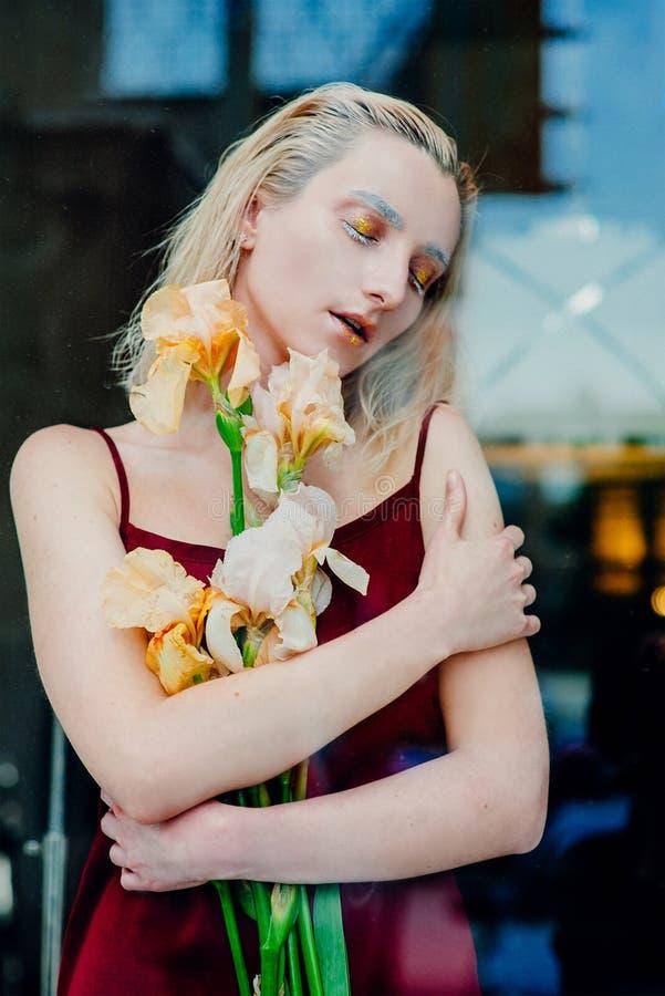 年轻白肤金发的可爱的妇女的画象有虹膜的在玻璃后开花 免版税库存照片