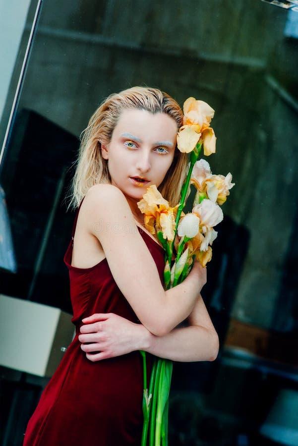 年轻白肤金发的可爱的妇女的画象有虹膜的在玻璃后开花 免版税库存图片