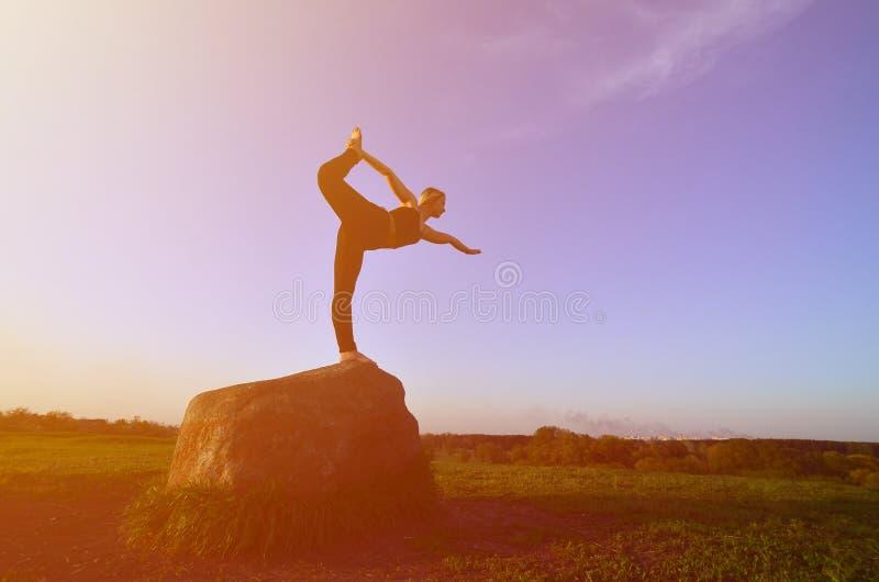 年轻白肤金发的女孩剪影体育衣服实践瑜伽的在美丽如画的青山在日落的晚上 库存图片