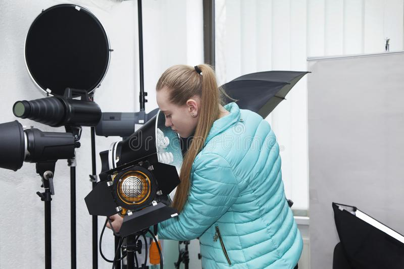 年轻白肤金发的女孩在专业照片设备商店考虑永久演播室光灯与圆的反射器的 库存照片