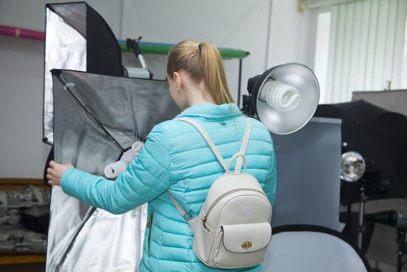 年轻白肤金发的女孩在专业照片设备商店选择永久演播室照片光灯与方形的反射器的 免版税库存图片