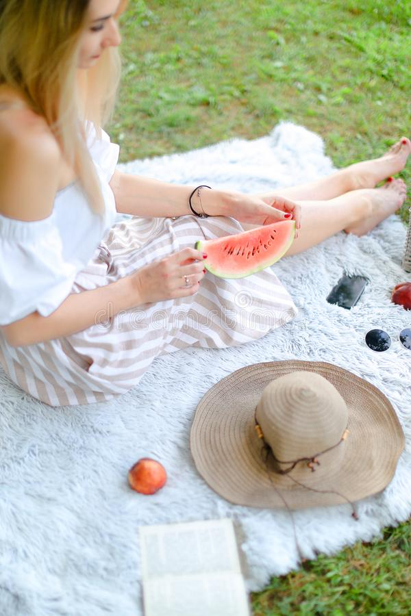 年轻白肤金发的女孩坐格子花呢披肩在果子和帽子附近,吃西瓜,草在背景中 库存照片