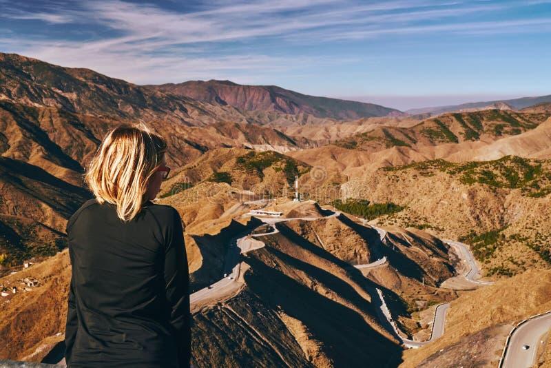 年轻白肤金发的女孩思考在提齐乌祖省n提什卡山口山口全景在摩洛哥 免版税库存图片