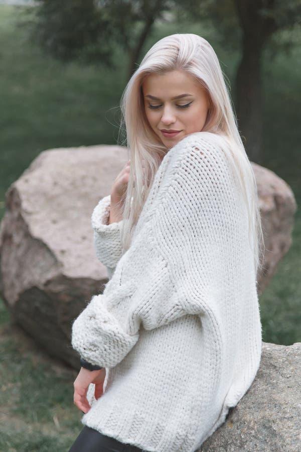 年轻白肤金发的女性佩带的被编织的白色毛线衣 妇女时尚概念 免版税图库摄影
