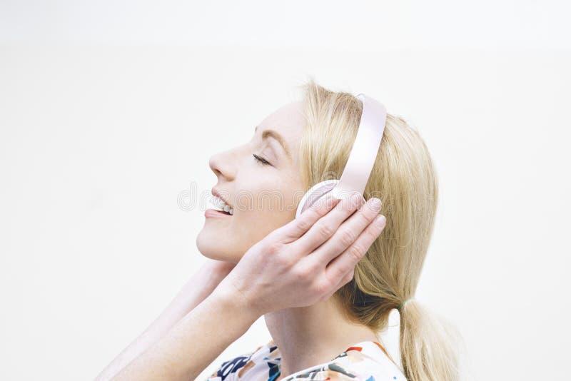 年轻白肤金发的女性听到在耳机愉快的音乐被启发移动 库存照片