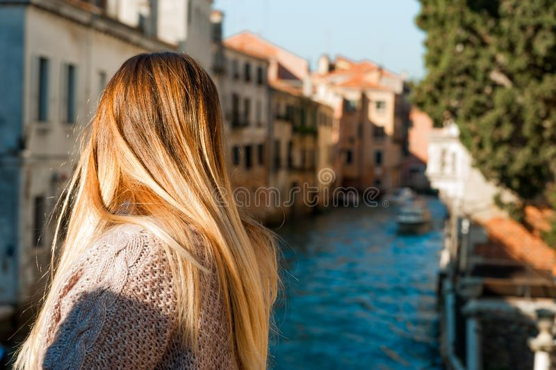 年轻白肤金发的妇女在看威尼斯运河的便装样式穿戴了看见从后面 库存照片