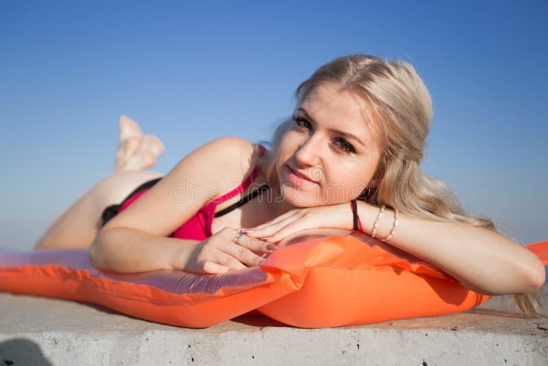 年轻白肤金发的妇女在看照相机的水池木筏晒日光浴 免版税库存图片