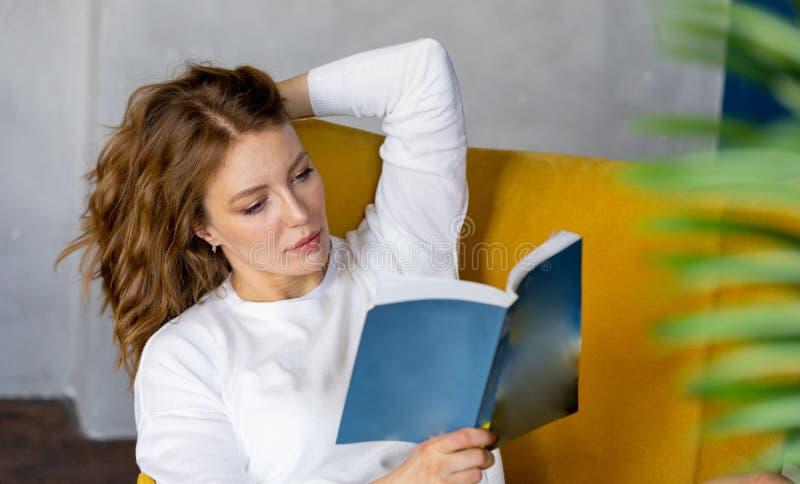 年轻白肤金发的妇女看书在家和坐在黄色扶手椅子 库存图片