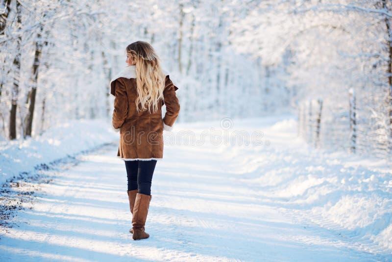 年轻白肤金发的妇女走的冬天公园 免版税图库摄影