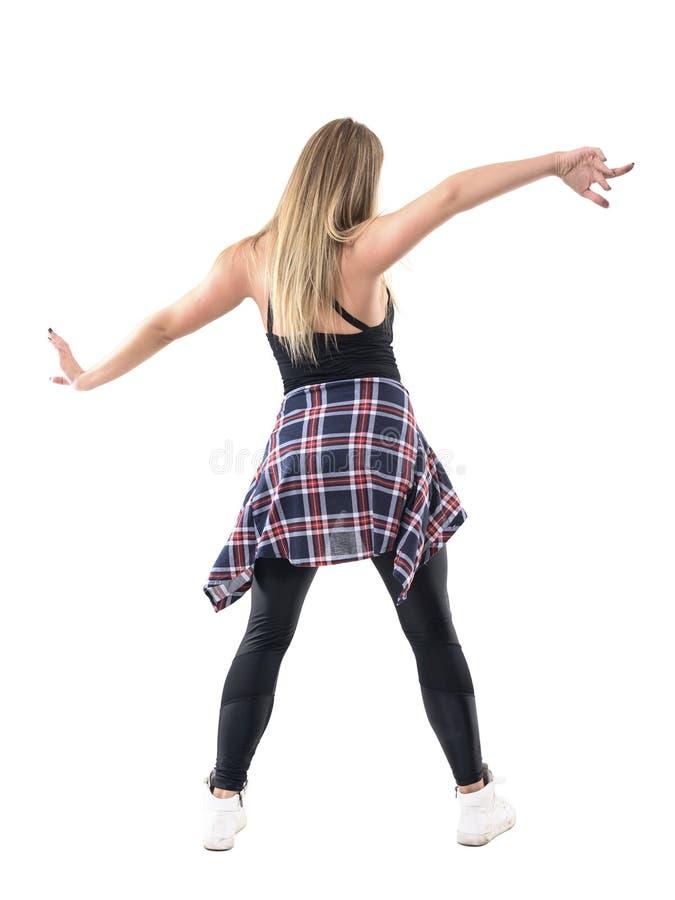 年轻白肤金发的妇女跳舞背面图与被伸出的传播的武装姿势 库存照片