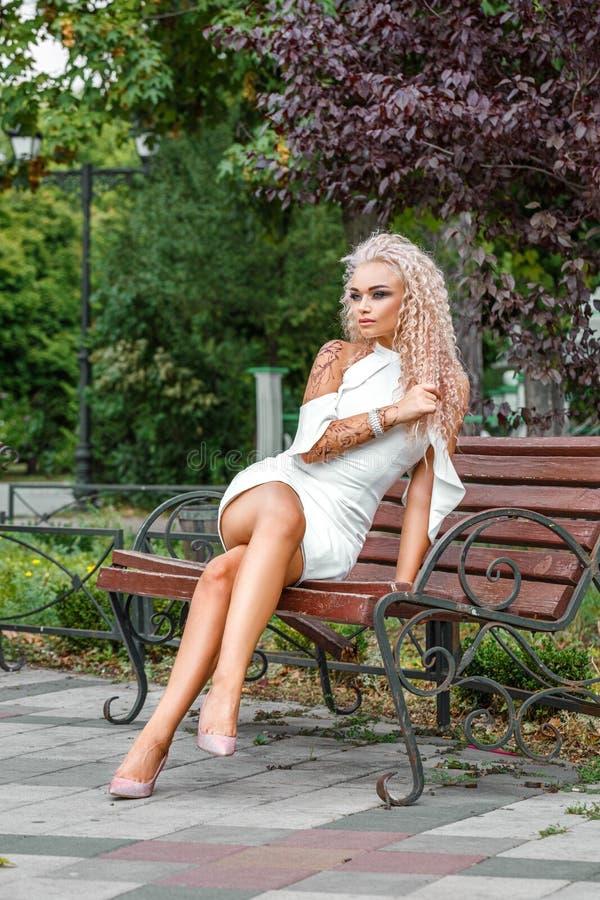 年轻白肤金发的妇女高档时尚射击白色短的礼服的 免版税库存图片