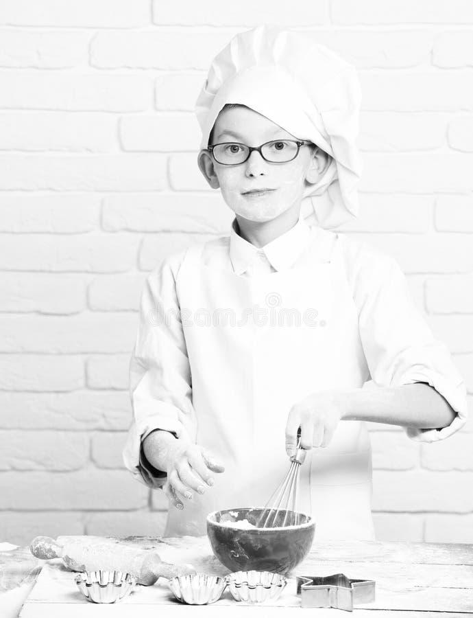 年轻白色制服和帽子的男孩小逗人喜爱的厨师厨师在与站立与滚针的玻璃的愉快的面孔近的桌 图库摄影