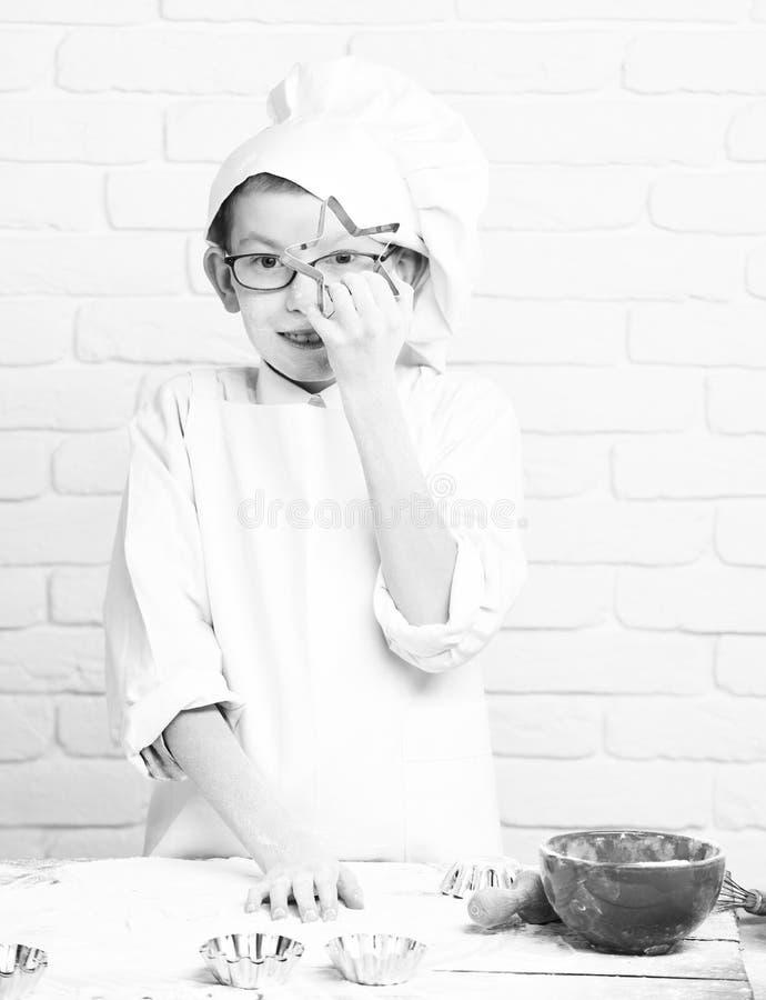 年轻白色制服和帽子的男孩小逗人喜爱的厨师厨师在与站立近的桌与的玻璃的被弄脏的面孔面粉 免版税库存照片