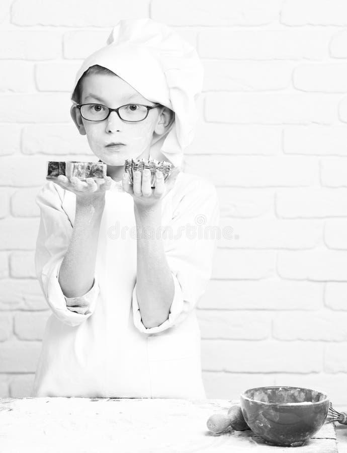 年轻白色制服和帽子的男孩小逗人喜爱的厨师厨师在与站立近的桌与的玻璃的被弄脏的面孔面粉 库存图片