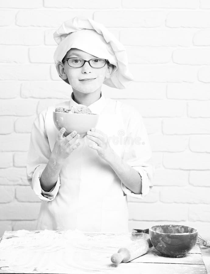 年轻白色制服和帽子的男孩逗人喜爱的厨师厨师在与站立在与辗压的桌附近的玻璃的被弄脏的面孔面粉 库存照片