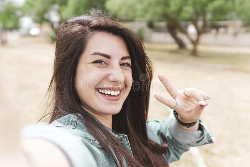 年轻的嬉皮士女人自拍 — 漂亮的旅行女孩拍照,展示两根手指 — 在环球巡游中虚度假 免版税库存图片