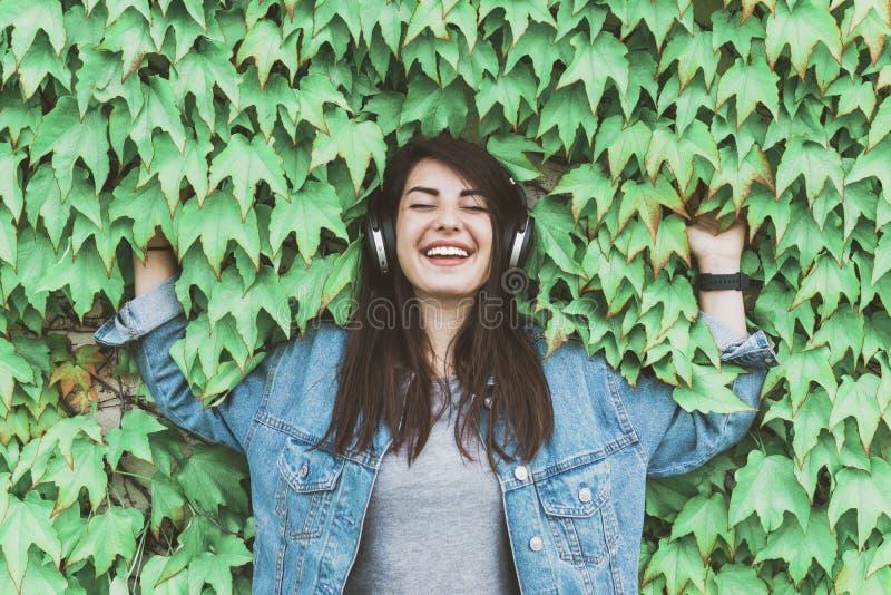 年轻的嬉皮士女孩听贴在常青藤墙上的音乐 — 在城市公园里,漂亮的女人戴着耳机放松 图库摄影