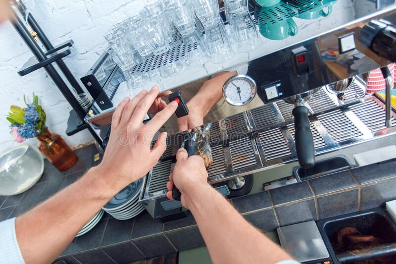 年轻的成年咖啡师在餐馆工作,煮咖啡 免版税库存图片