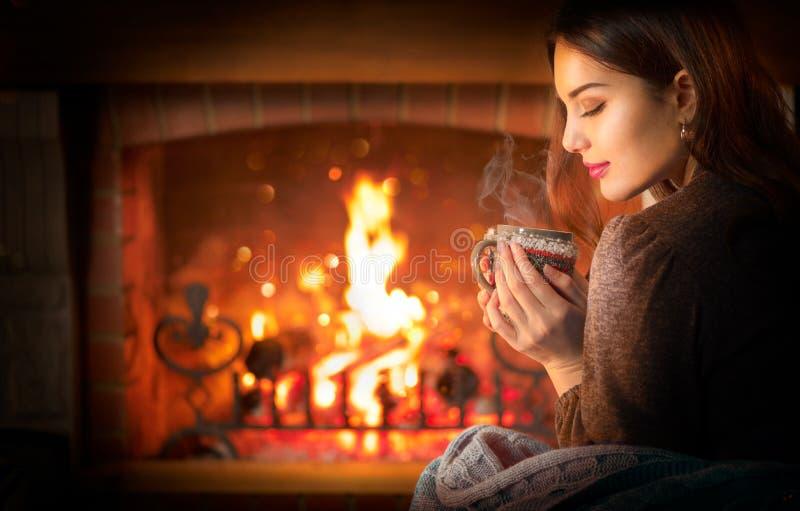 年轻的漂亮圣诞女人坐在家中昏暗的房间里的壁炉旁,喝着大杯里的热饮 免版税库存图片