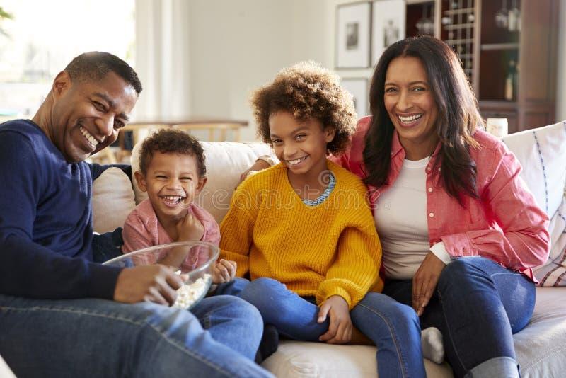 年轻的祖父母与笑他们的孙坐沙发在客厅吃玉米花和,正面图,接近的u 库存照片