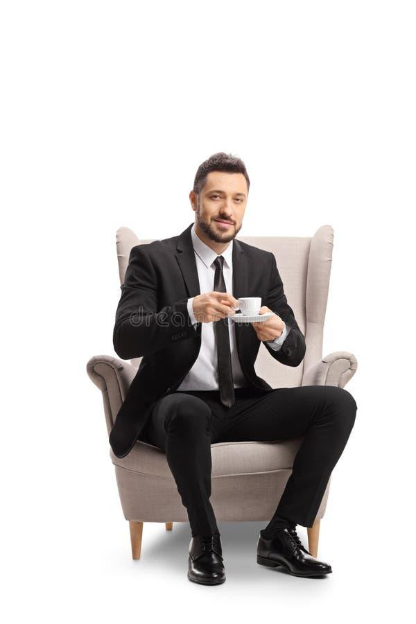 年轻的职业男士,身着西装,打着领带,坐在扶手椅上,手里拿着一杯特浓咖啡 库存照片